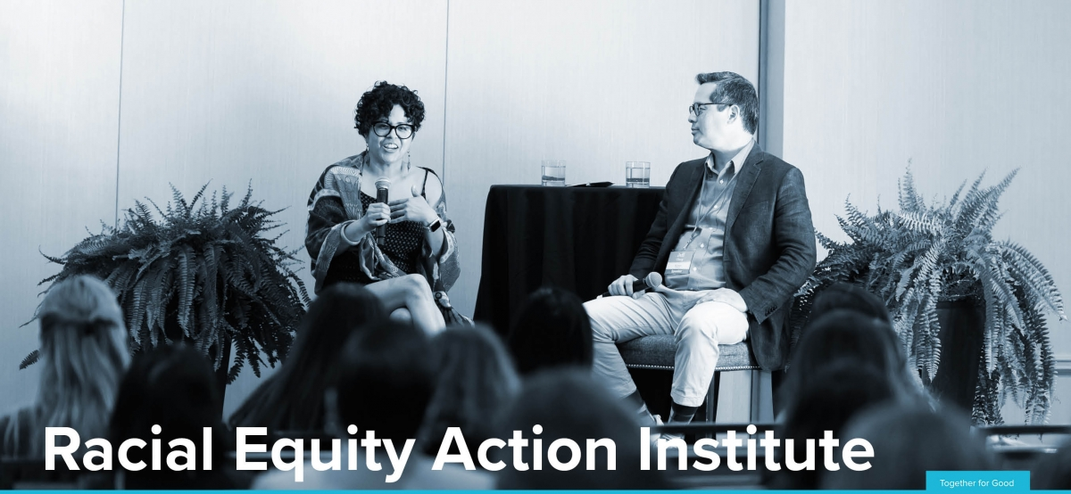 "Photo with two people in conversation and reads ""Racial Equity Action Institute"""